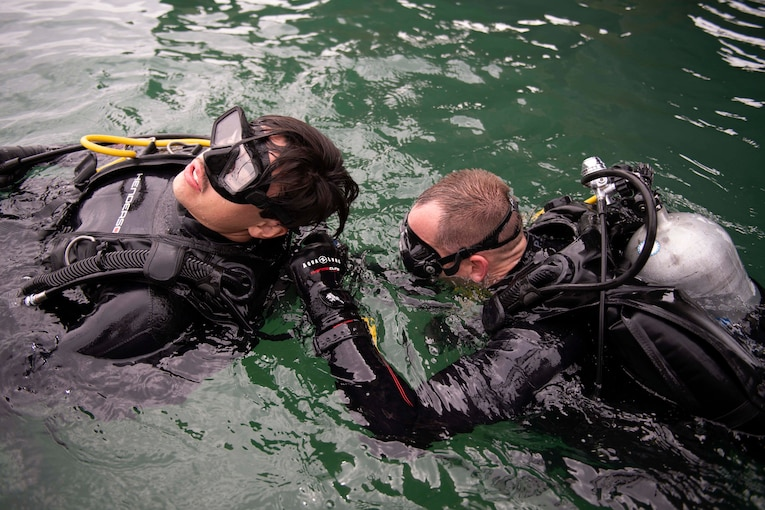 A sailor looks underwater while another sailor floats on his back.