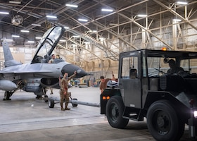 Airmen from the 310th Aircraft Maintenance Unit transport an F-16D Fighting Falcon to the flightline June 23, 2020, at Luke Air Force Base, Ariz.