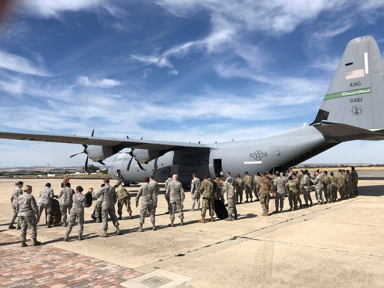 A photograph of multiple California Air National Guard airmen waiting to board  a C-130J Super Hercules military aircraft at the Paso Robles Municipal airport.