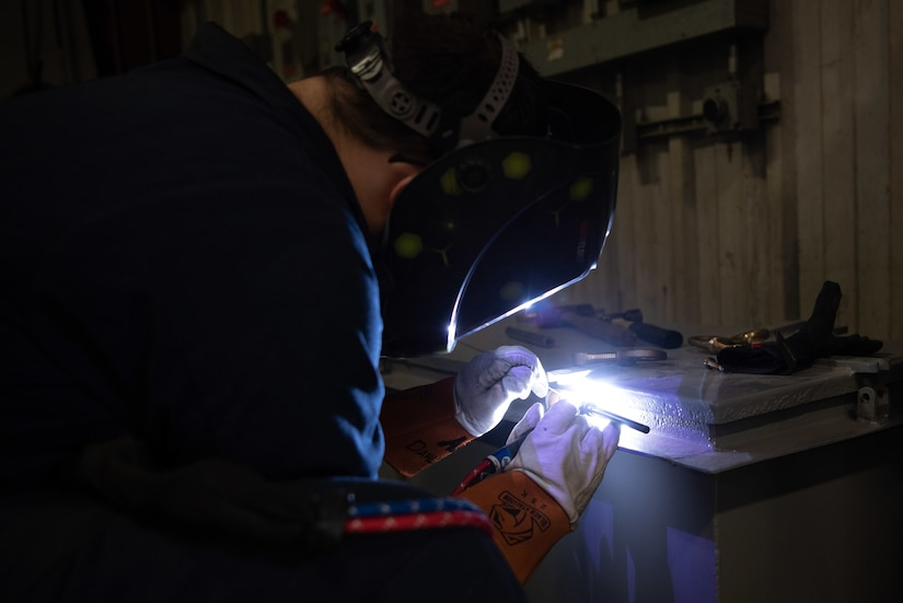 A man wearing protective gear welds an object.