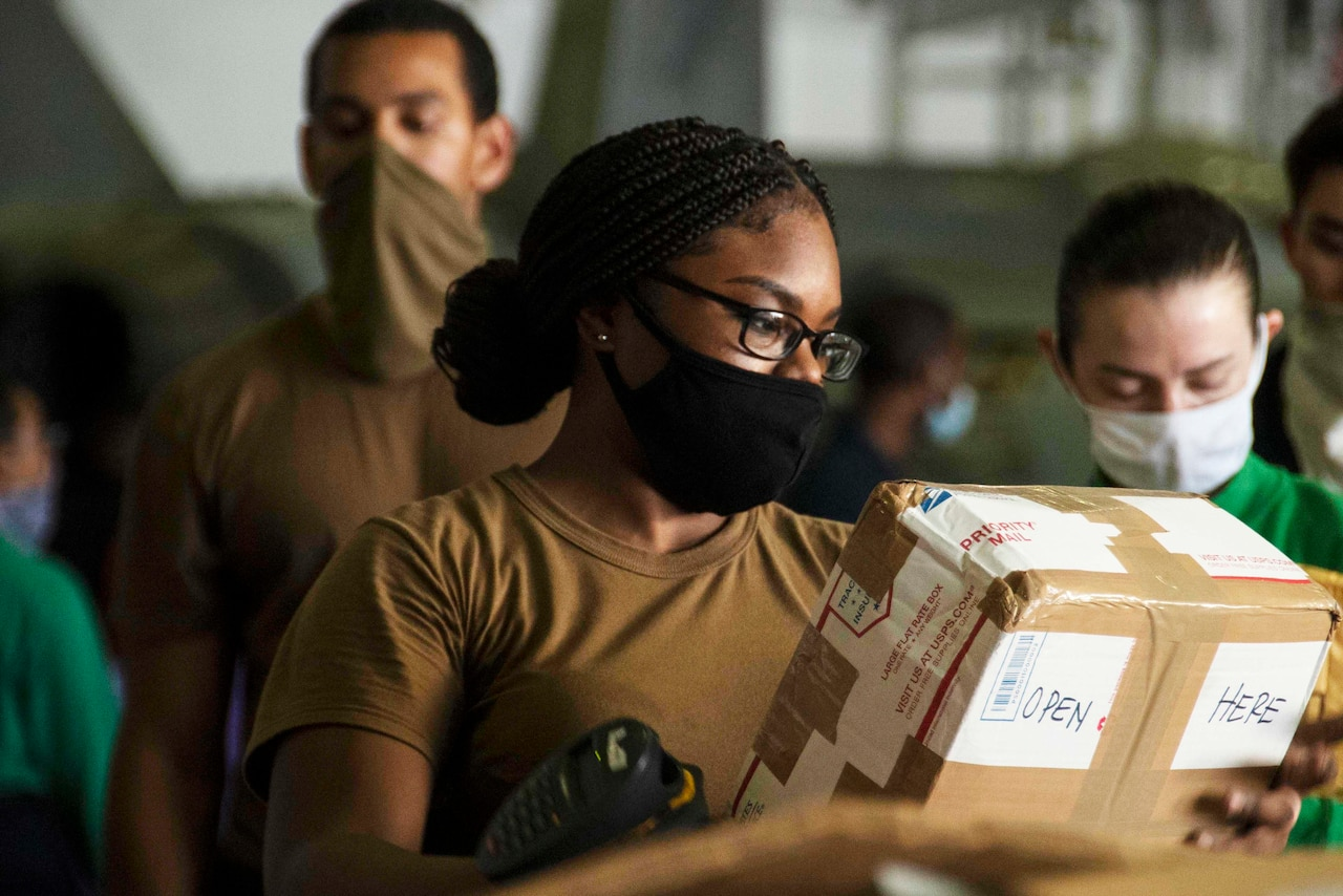 A sailor, wearing a face mask, sorts mail in the hangar bay of a ship during a replenishment at sea. Other sailors, also wearing face masks, are in the background.