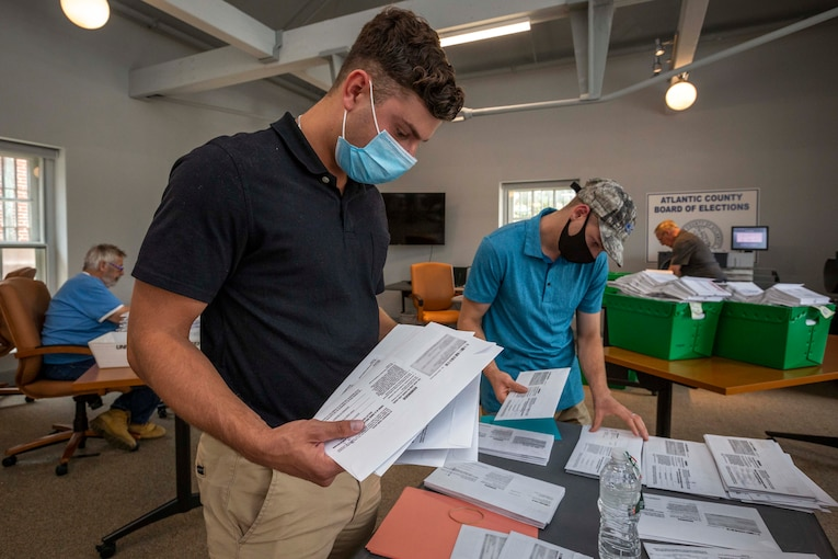 A soldier wearing a mask and another soldier behind him help alphabetize ballots.
