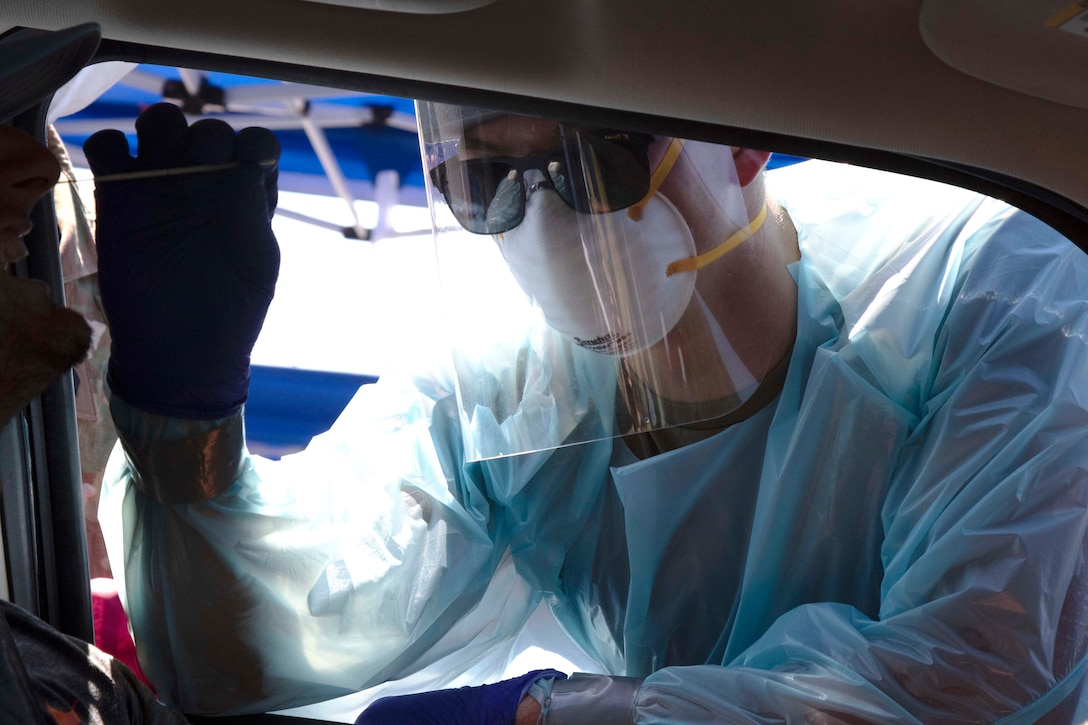 A guardsman wearing personal protective equipment administers a COVID-19 test on a passenger through a car window.