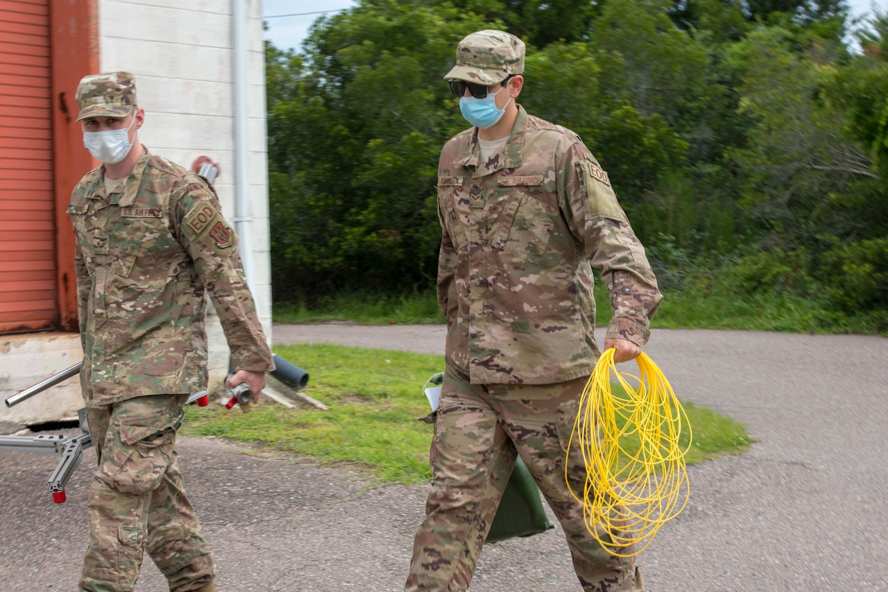Airmen wearing face masks walk side by side. One is carrying equipment, and the other is carrying a rolled-up length of yellow wire.
