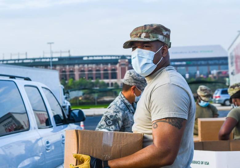 Guardsmen prepare family food boxes for distribution.
