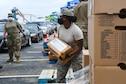 Guardsmen prepare family food boxes for distribution.