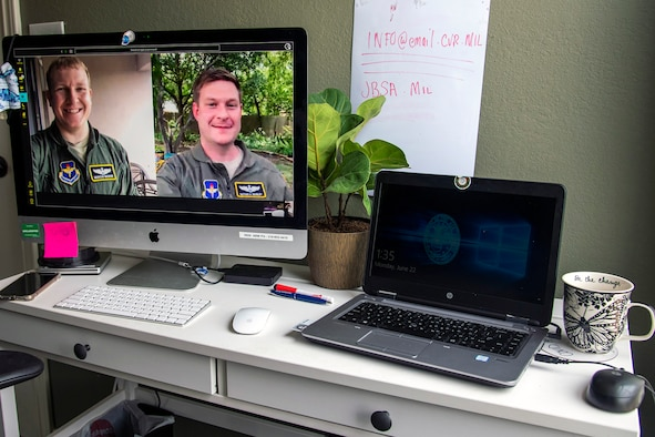 Maj, Marcus Mosher (left) and Maj. Nathan Moseley (right) participate in a video chat.