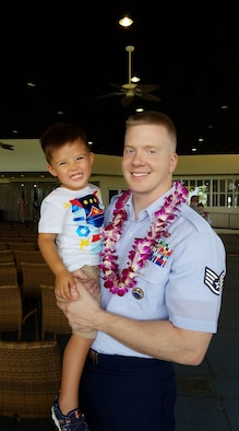 Tech. Sgt. Josef Margetiak, 614th Air Operations Center section chief, poses for a photo with his son at his Community College of the Air Force graduation. In late 2018, Margetiak was diagnosed with testicular seminoma cancer, and once cleared, he was diagnosed again in 2019. Throughout his fight with testicular cancer, Margetiak has been motivated by both his family and his goals to become a Physical Therapy to help others be the best versions of themselves, while pushing forward resiliently to complete his everyday duties. (Courtesy photo)