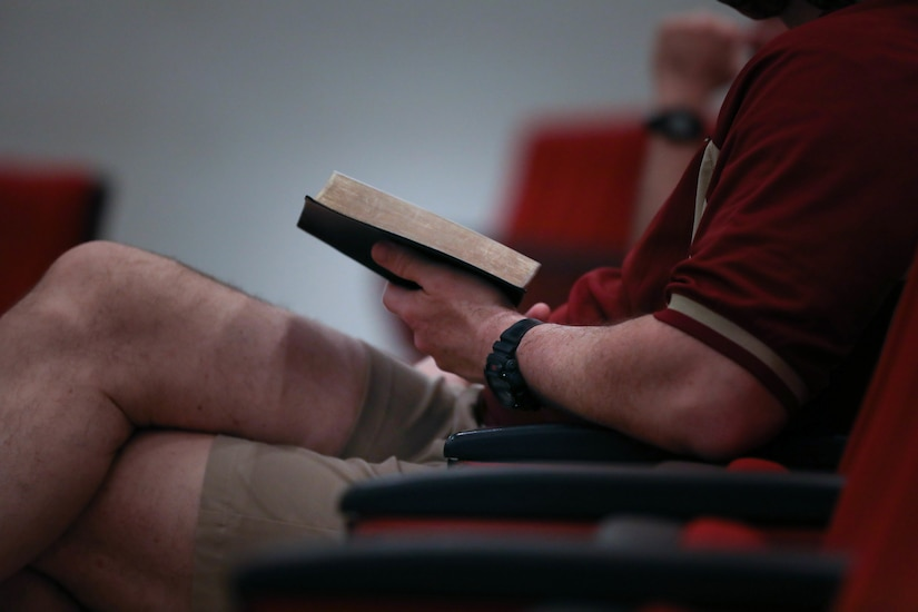 A man seated in a pew holds a book open during a chapel service.