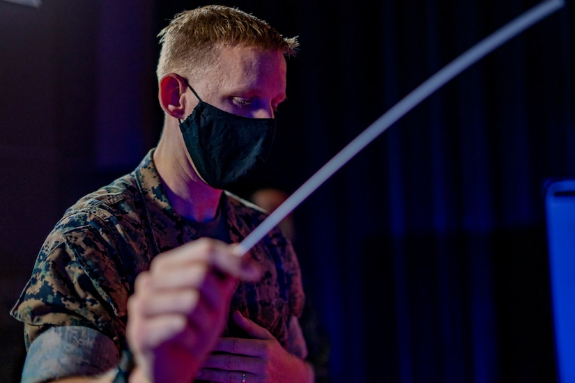A Marine holds out a musical baton.