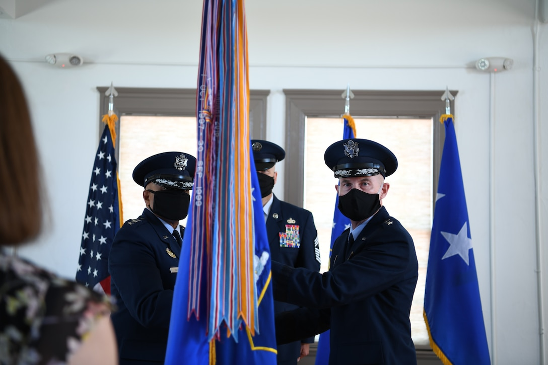 """Lt. Gen. Anthony Cotton, deputy commander of Air Force Global Strike Command, presents the guidon to Maj. Gen. Michael Lutton, the new 20th Air Force commander, during a change of command ceremony, 8 July, 2020, F. E. Warren Air Force Base, Wyo. During the ceremony, Maj. Gen. Michael J. Lutton took command of 20th Air Force from Maj. Gen. Ferdinand """"Fred"""" B. Stoss. (U. S. Air Force photo by Senior Airman Braydon Williams)"""