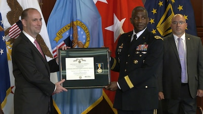 White man in suit and black man in Army dress uniform hold a framed certificate and medal in front of U.S. and DLA flags