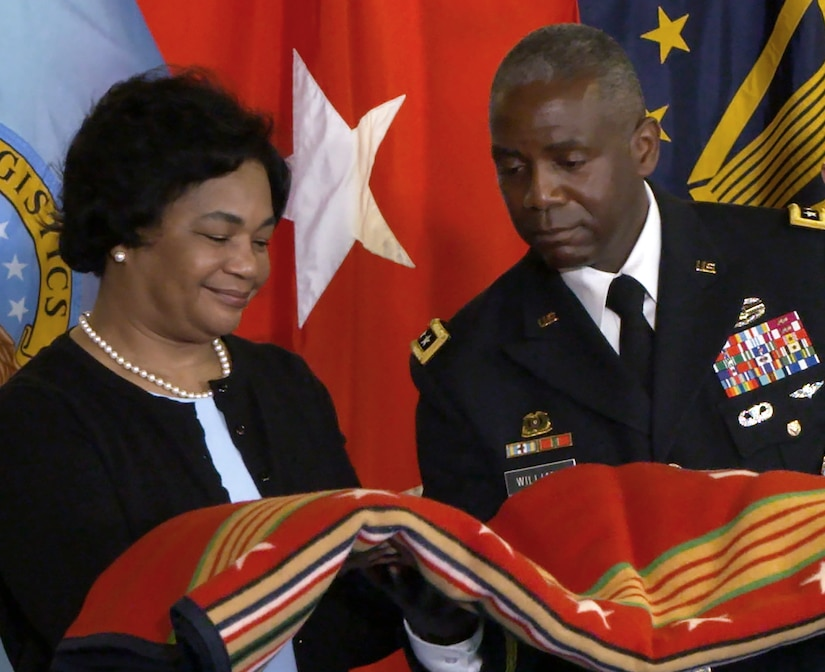 Black man and woman stand in front of the U.S., DLA and 3-star general flags holding a red blanket with multicolored stars and stripes.