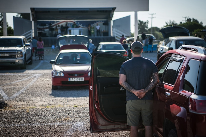 A group of people stand next to parked cars.