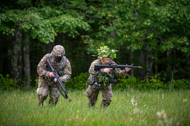 Two guardsmen in camouflage hold weapons in a forest-like area.