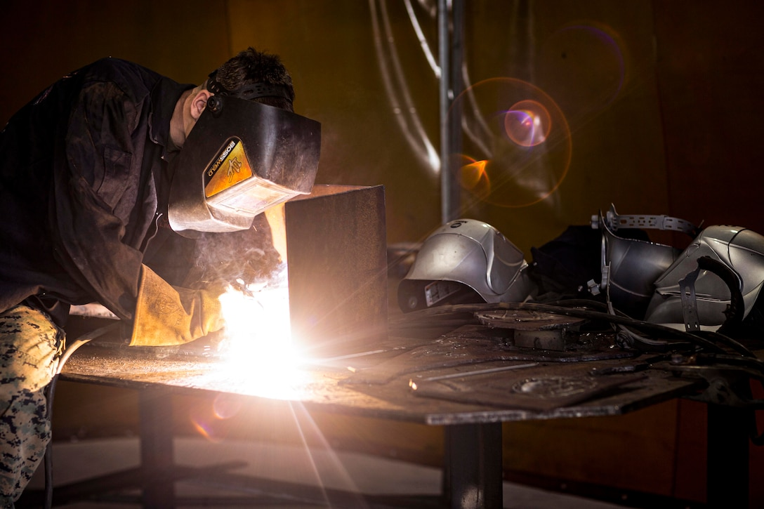 A Marine in protective gear practices welding.