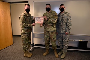 U.S. Air Force Col. Jeffrey Nelson, left, 60th Air Mobility Wing commander, and Chief Master Sgt. Stephen Scofield, right, 60th Maintenance Squadron squadron superintendent, recognize Staff Sgt. Cesar Torres, 60th Communications Squadron network control center technician, as the Warrior of the Week, July 7, 2020, at Travis Air Force Base, California. The Warrior of the Week program recognizes outstanding Airmen who have made significant contributions to their unit. (U.S. Air Force photo by Airman 1st Class Cameron Otte)