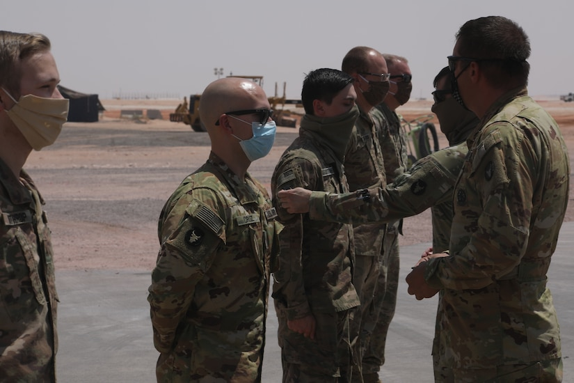 """U.S. Army Soldiers assigned to Task Force Javelin were awarded the Shoulder Sleeve Insignia  of the 34th """"Red Bull"""" Infantry Division on July 2, 2020 in the Kingdom of Saudi Arabia. The SSI was awarded to 21 members of TFJ for their service in a designated combat zone. (U.S. Army National Guard photo by Sgt. Trevor Cullen)"""
