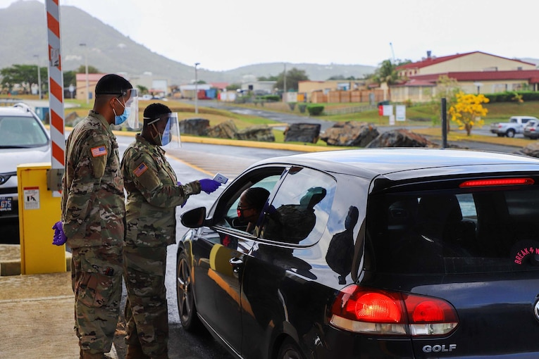 Several guardsmen wearing masks and gloves scan the temperature of a service member while she remains in her car.