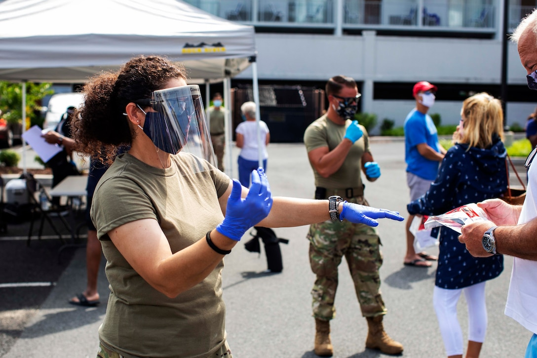 An airman wearing personal protective equipment provides directions to a pedestrian at a walk-up testing site.