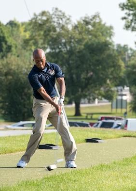 Man hitting golf ball on the golf course.