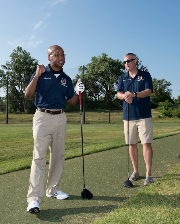 Men standing on golf course.