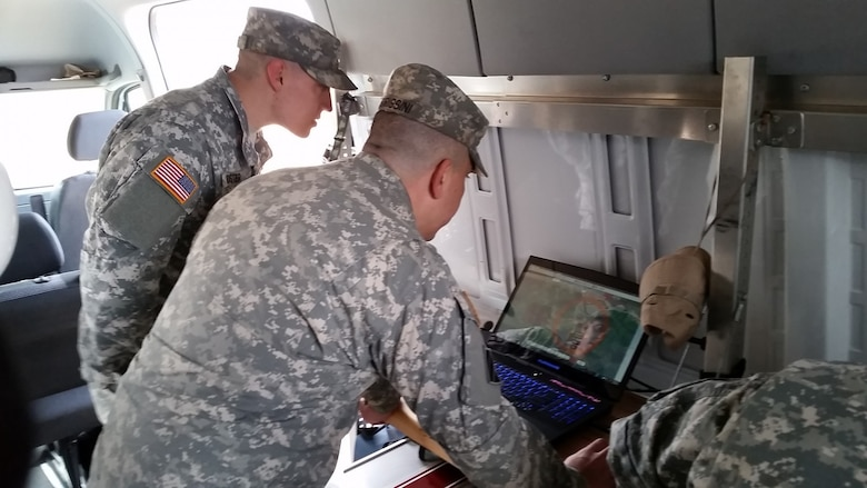 Two soldiers look over a model on a laptop.