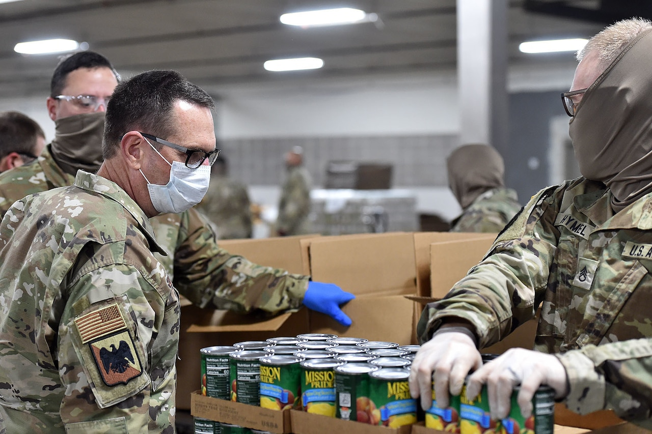 Several service members wearing face masks check the contents of a case  of canned goods.
