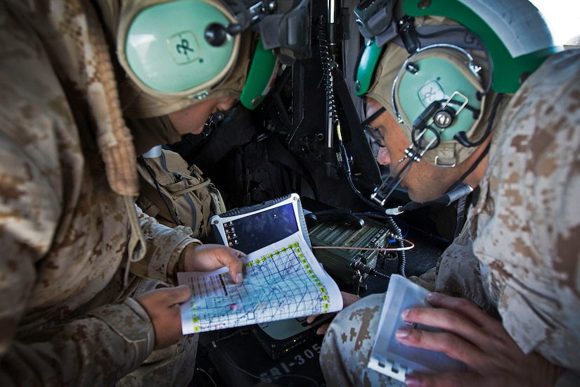 Two service members wearing aviation headgear, crouch near each other and look at a map.