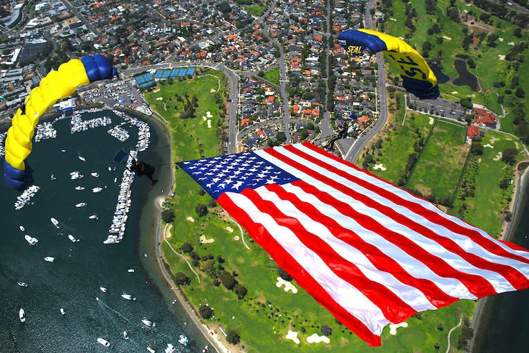 Sailors free fall while holding up the American flag over a city.