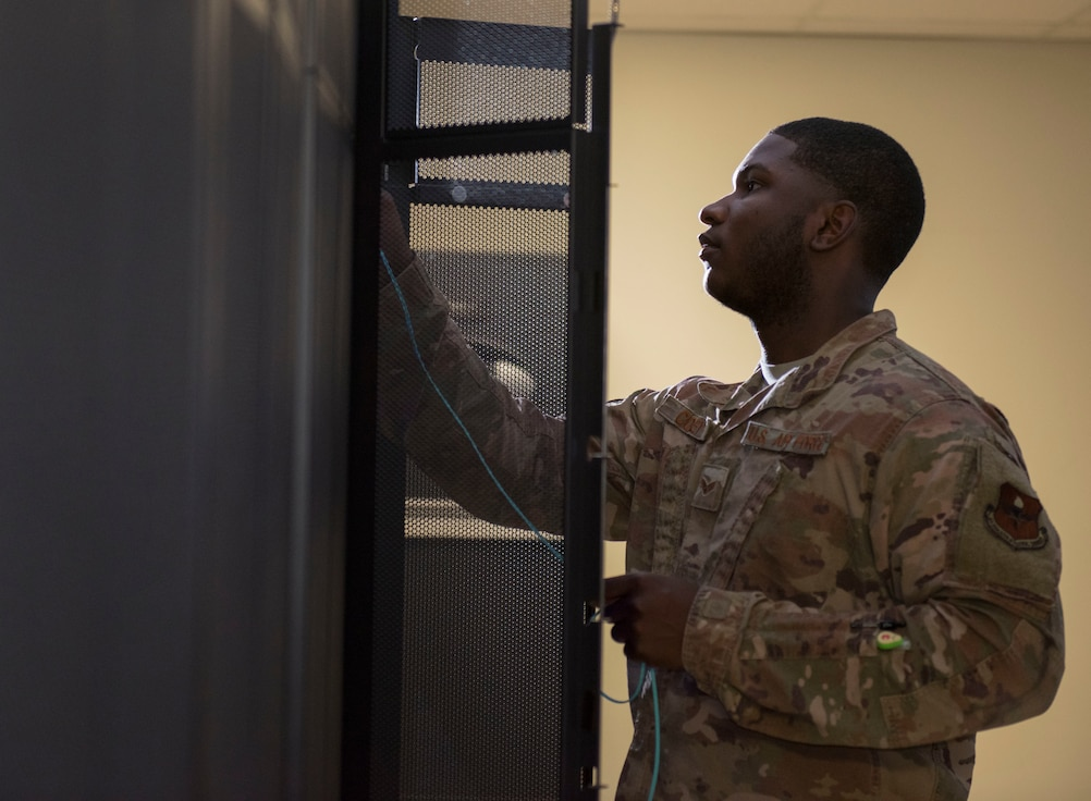 Senior Airman Justin Coley, 49th Communications Squadron unit security manager, connects fiber optic cables to the base network switches, June 30, 2020, at the base network control center on Holloman Air Force Base, N.M. The 49th Communications Squadron consists of many teams who are responsible for maintaining network connectivity, managing and installing any base communication devices, and monitoring the security of base network information. (U.S. Air Force photo by Airman 1st Class Quion Lowe)