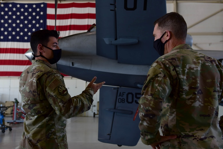 A Airman briefs a commander in front of an MQ-9 Reaper tail and United States flag.