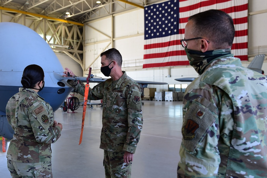 An Airman briefs two commanders in front of an MQ-9 Reaper nose and United States flag.