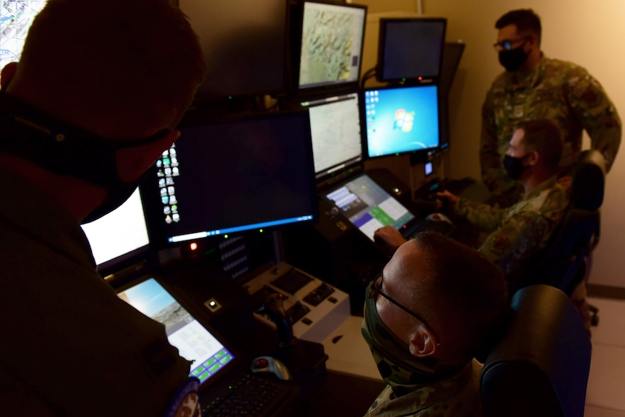 99th Air Base Wing leadership sit in an MQ-9 Reaper flight simulator with instructors.