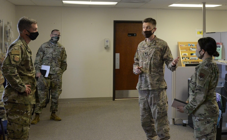 Airmen brief 99th Air Base Wing leadership in the personnel flight trailer's front room.