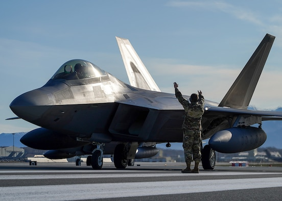 U.S. Air Force Staff Sgt. Christopher Graham, 3rd Wing crew chief, marshalls an F-22 Raptor on the flight line at Joint Base Elmendorf-Richardson, Alaska May 5, 2020. The 90th Fighter Squadron and 90th Aircraft Maintenance Unit recently launched 168 sorties in four days, highlighting their rapid mobility capabilities and response readiness during COVID-19 and the ability to generate combat airpower at a moment's notice to ensure regional stability throughout the North American Aerospace Defense Command Region and Indo-Pacific. (U.S. Air Force photo by Tech. Sgt. Westin Warburton)