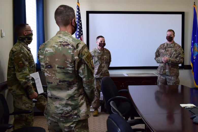 Civil Engineering Airmen brief 99th Air Base Wing Leadership in a conference room.