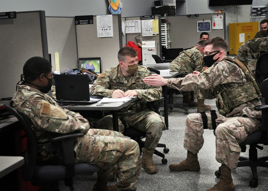 (left to right) Members of the 445th Security Forces Squadron, Staff Sgt. Daryn Weatherspoon, unit training instructor; Tech. Sgt. Jacob McCorkle, lead unit trainer; and Staff Sgt. Mitchiner Underhill, fire team member, perform a tabletop evaluation to test Airman's knowledge of cover and concealment, flanking procedures and moving as a firing team, June 6, 2020.  Discussions like these are now completed in small groups to comply with social distancing guidelines.