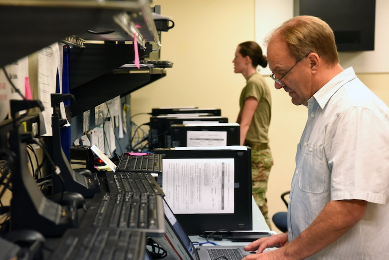 James Johnson and Airman 1st Class Savannah Coon, 31st Communications Squadron client systems technicians, reimage computers at Aviano Air Base, Italy, July 9, 2020. Reimaging computers was an important factor during the COVID-19 crisis. (U.S. Air Force photo by Staff Sgt. Heidi Goodsell)