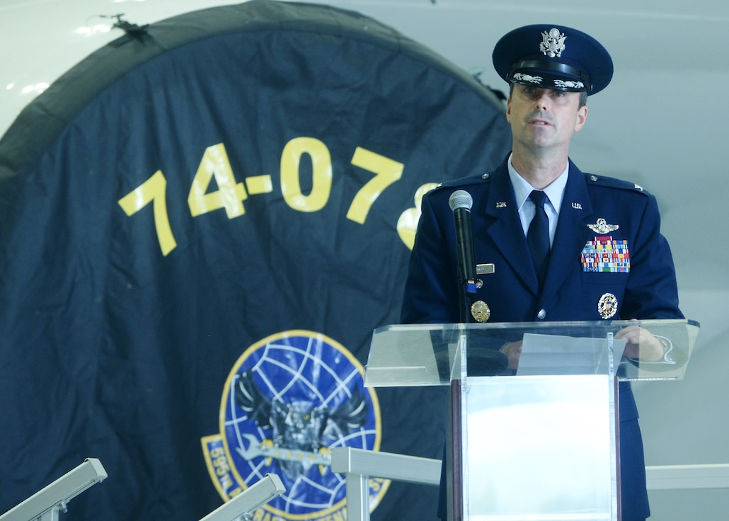 Airman stands at podium in front of E-4B aircraft