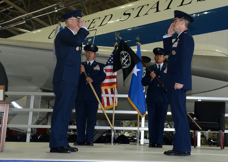 Airmen salute one another in front of E-4B aircraft
