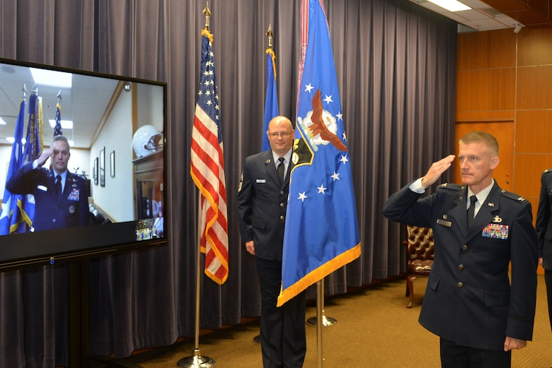 Lt. Gen. Timothy Haugh, Sixteenth Air Force (Air Forces Cyber) commander, salutes Col. Brian Pukall, 557th Weather Wing commander, through a video conference link as he relinquishes command of the wing during a change of command ceremony at the 557th Weather Wing headquarters building, Offutt Air Force Base, Nebraska, June 25, 2020.