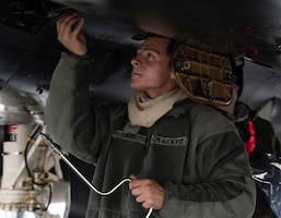 Airman 1st Class Hunter Laub, a 494th Fighter Squadron Aircraft Maintenance Unit crew chief, performs routine maintenance on an F-15E Strike Eagle at RAF Lakenheath, United Kingdom, June 10 2020.