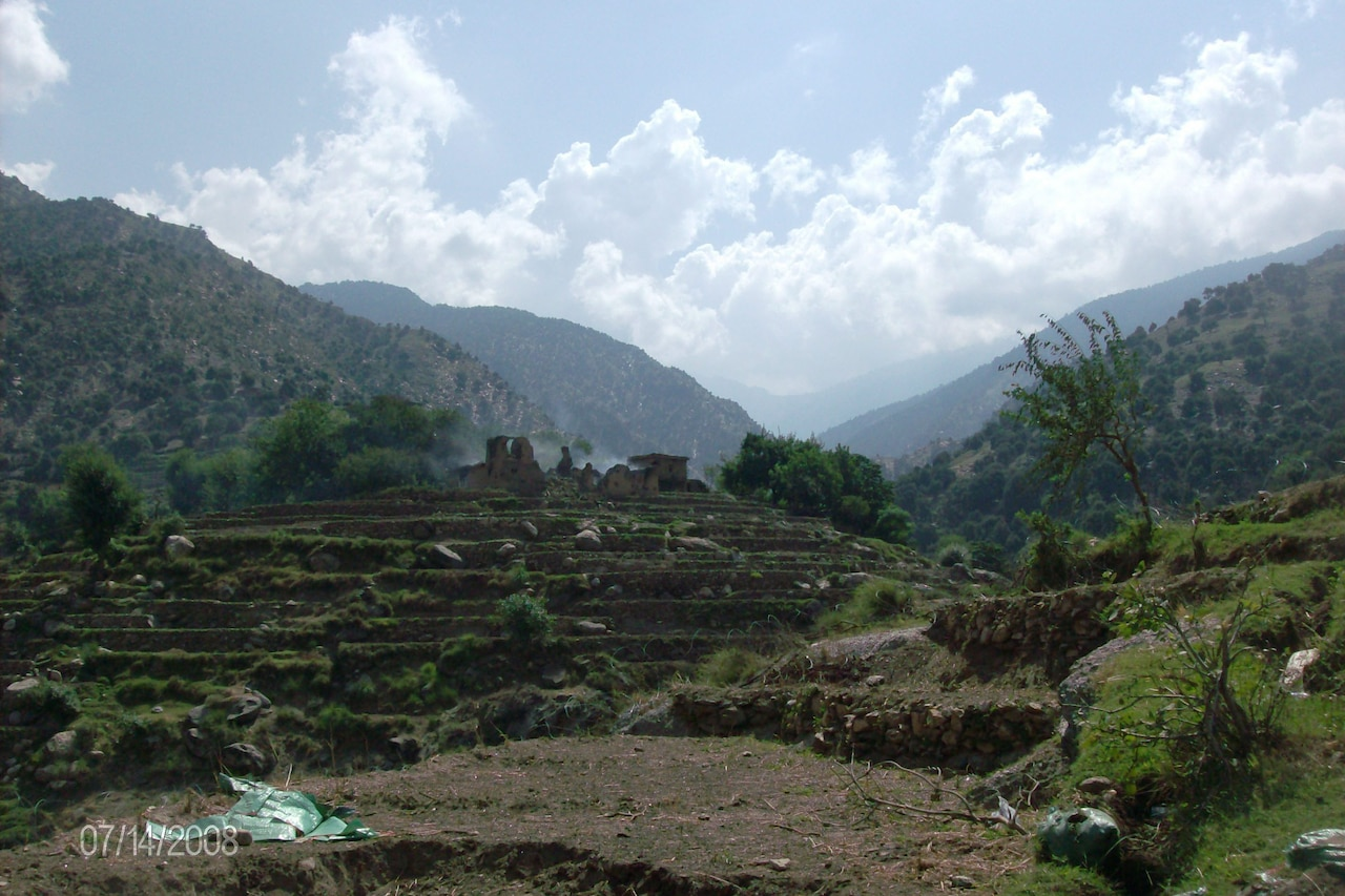 Dilapidated rock buildings sit atop a hillside in between mountains.