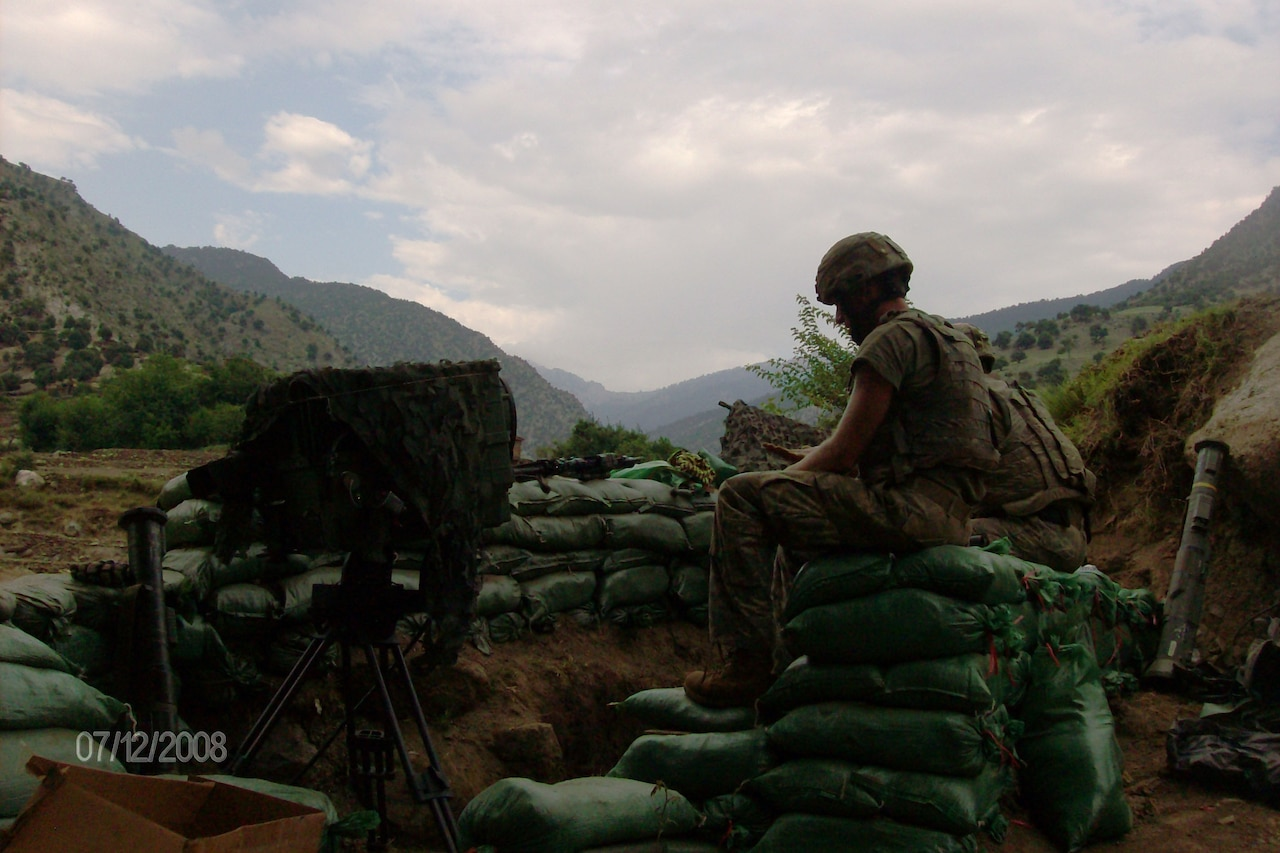 Two soldiers sit on sandbags. Mountains are in the background.