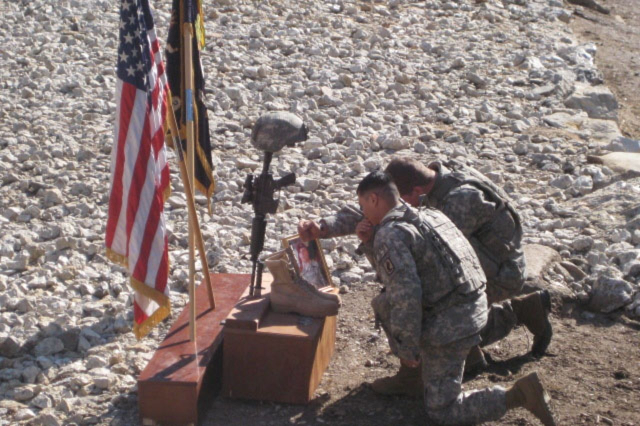 Two soldiers kneel in front of a memorial for a fallen comrade.