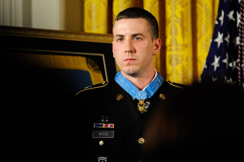 A man in a military uniform and wearing a medal stands at attention.