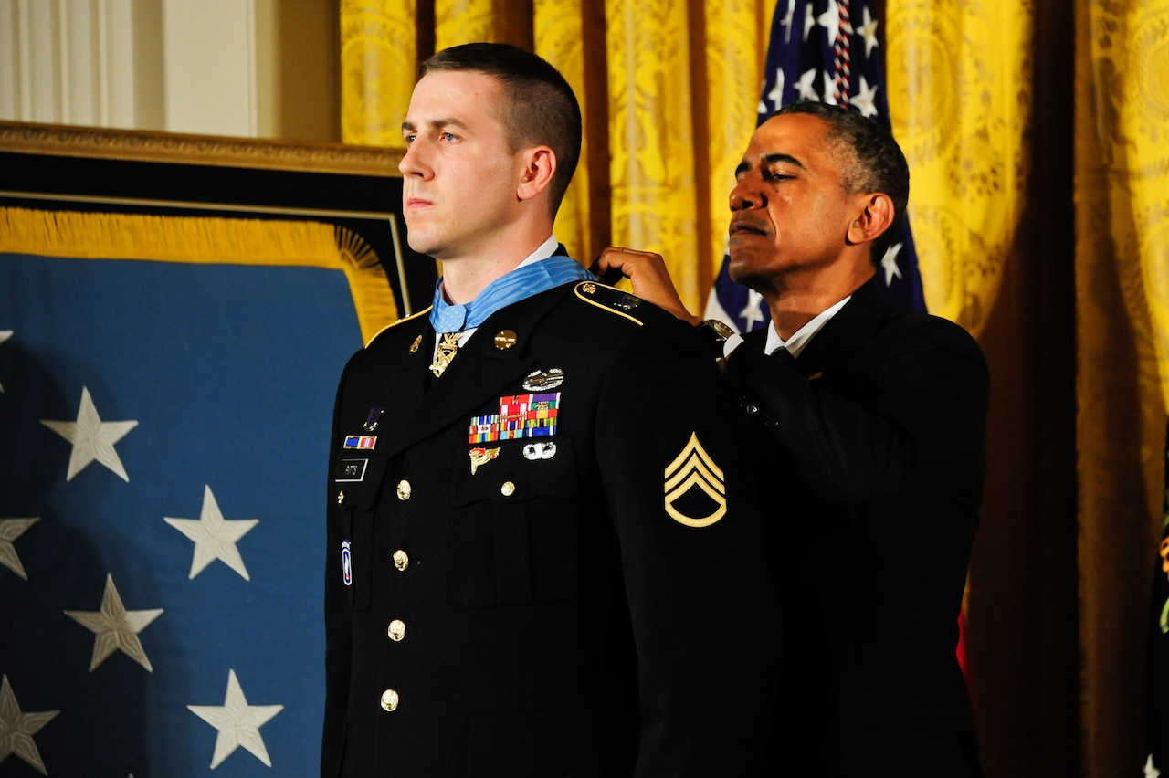 A man fastens a medal around a soldier's neck.