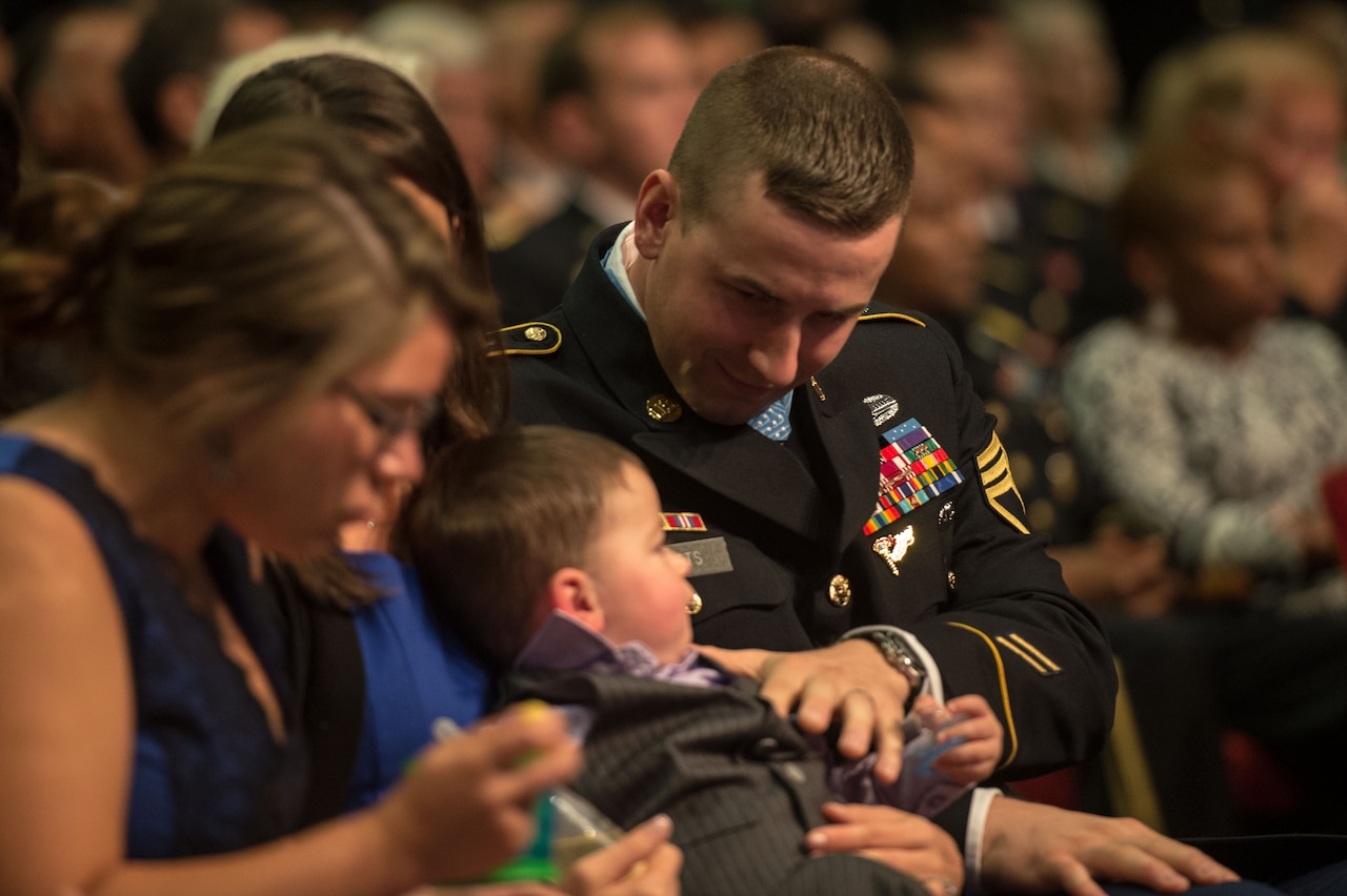 A soldier in a seated crowd puts his hand on his small son's chest.