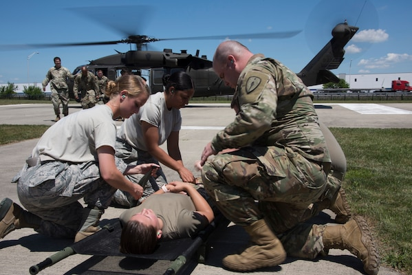 Airmen and Soldiers from the Indiana National Guard prepare to load a patient into a UH-60 Black Hawk helicopter during a medical transport exercise at the Johnson County Armory in Franklin July 2, 2020. Due to propeller wash, service members did not wear masks for safety reasons as the masks could cause debris interfering with helicopter propellers.